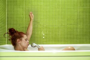 side view of woman in bathtub singing, enjoying bath and having fun.photo taken inside bathroom, green tile on the wall.